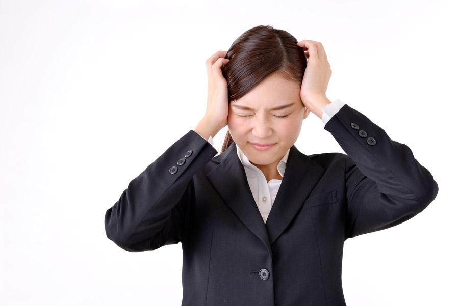 頭を抱えて悩む女性社員