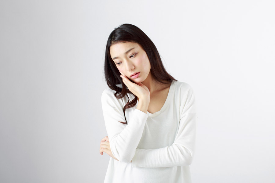 頬に手を当てて悩む日本人女性