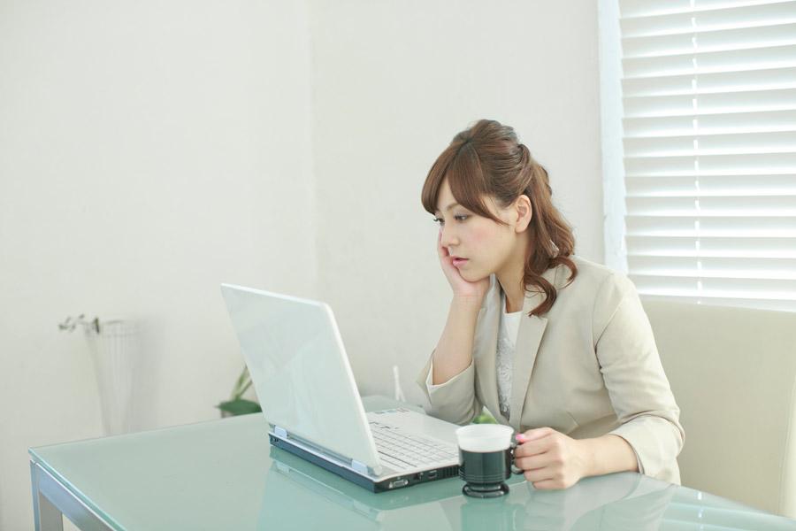 パソコンの画面を見ながら考え事をしている女性会社員