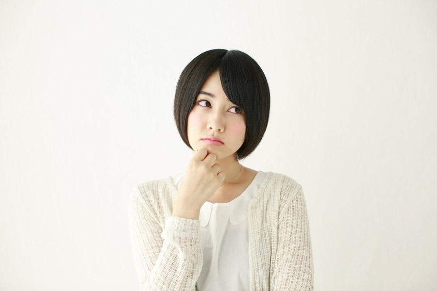 顎に手を当てながら悩んでいる日本人女性