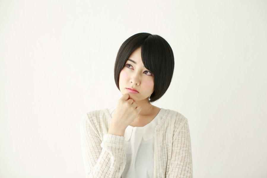 顎に手を当てながら思考中の日本人女性
